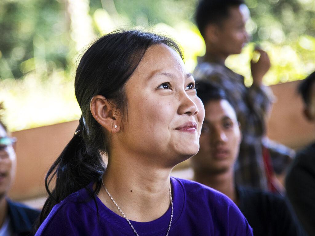Närbild av ung leende kvinna i lila t-shirt. I bakgrunden syns fler människor.