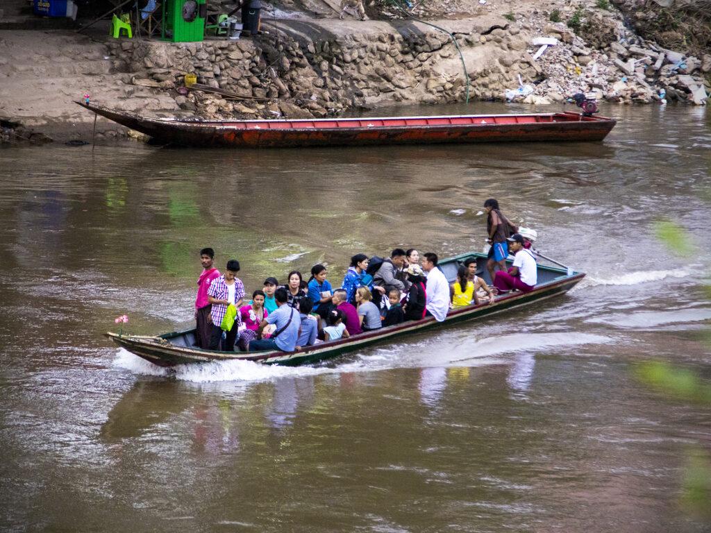 Bild av en lång motorbåt som åker i en flod. I båten sitter flera vuxna och barn.