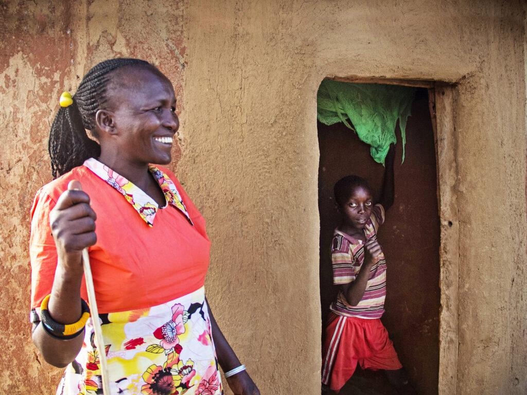 Leende kvinna står framför ett hus. I dörröppningen till huset står en pojke och tittar ut.