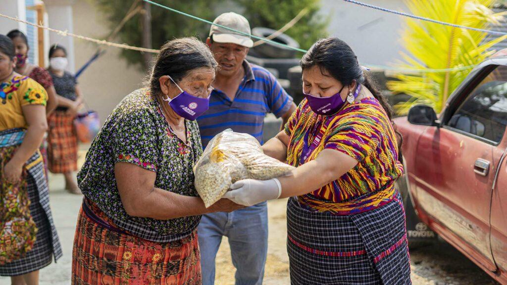 Två äldre kvinnor i munskydd bär en stor påse med spannmål av något slag. I bakgrunden syns människor och en bil.