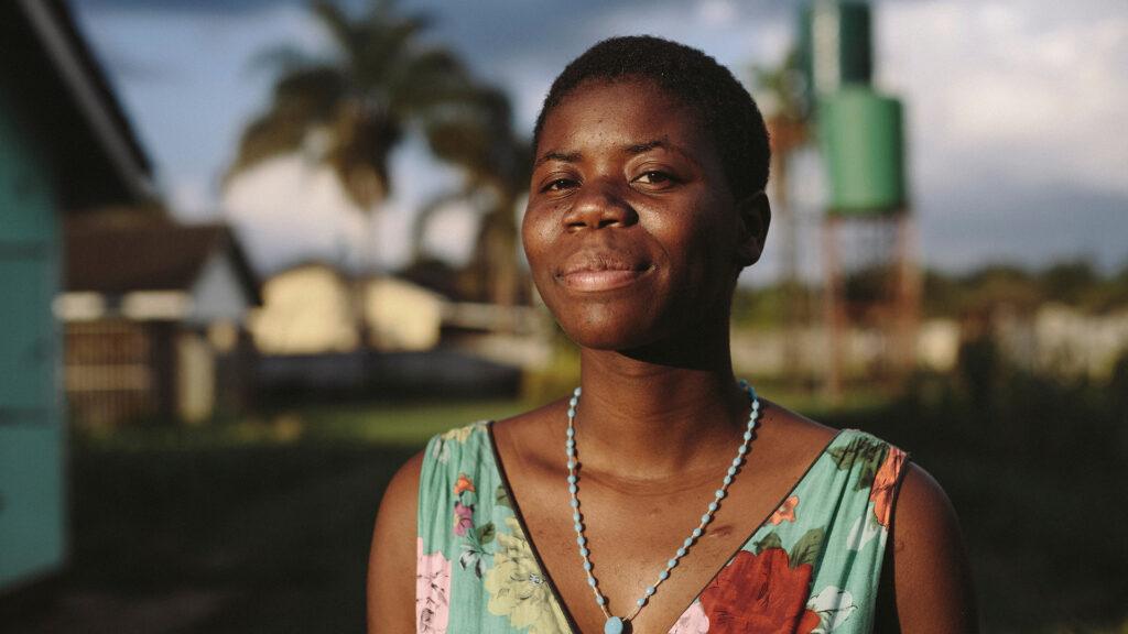 Kvinna i Zimbabwe tittar in i kameran. I bakgrunden syns låga byggnader och fält av gräs.