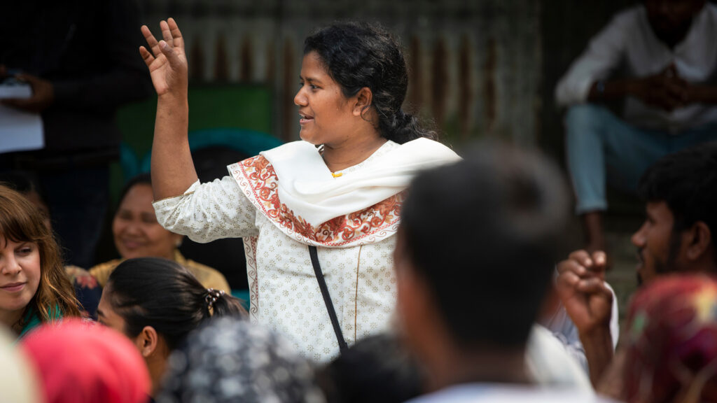 Kvinna som står upp i en grupp av människor. Hon pratar och gestikulerar med handen.