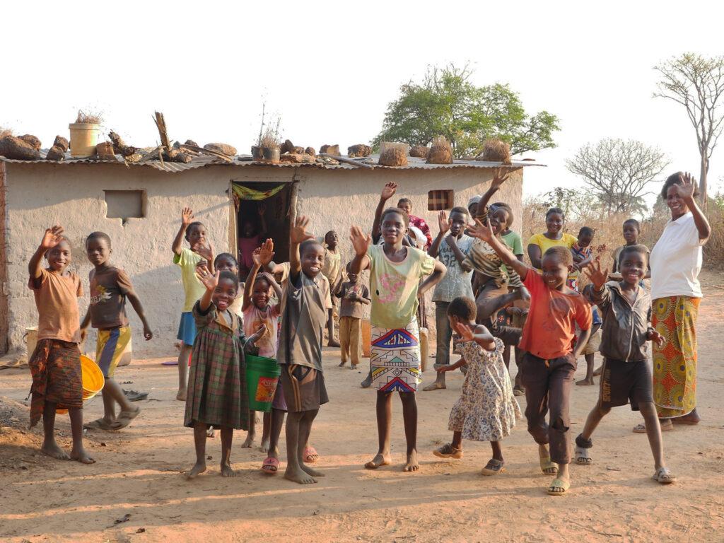 En stor grupp med leende och glada barn med händerna i luften står framför ett litet hus.