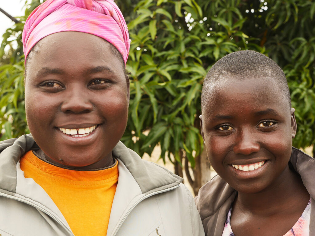Närbild av två leende ungdomar. Den ena har en rosa sjal på huvudet. Bakom dom syns gröna träd.