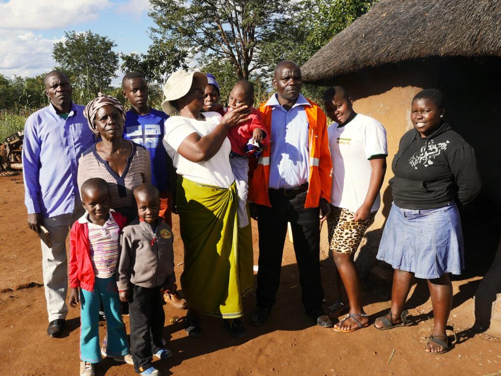En grupp med många människor, både vuxna och barn, ser in i kameran och står framför träd och ett hus med halmtak.