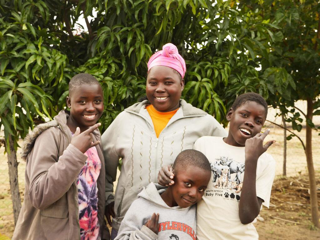 Fyra leende barn och ungdomar står tillsammans och ser in i kameran. Bakom dem syns några träd.
