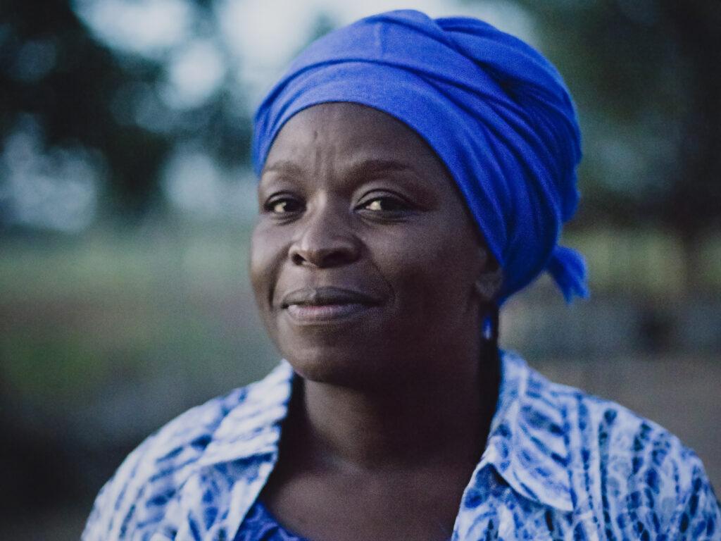 Närbild av en kvinna i skymning med blå sjal på huvudet som ser in i kameran. Bakom henne syns ett grönt fält och träd.