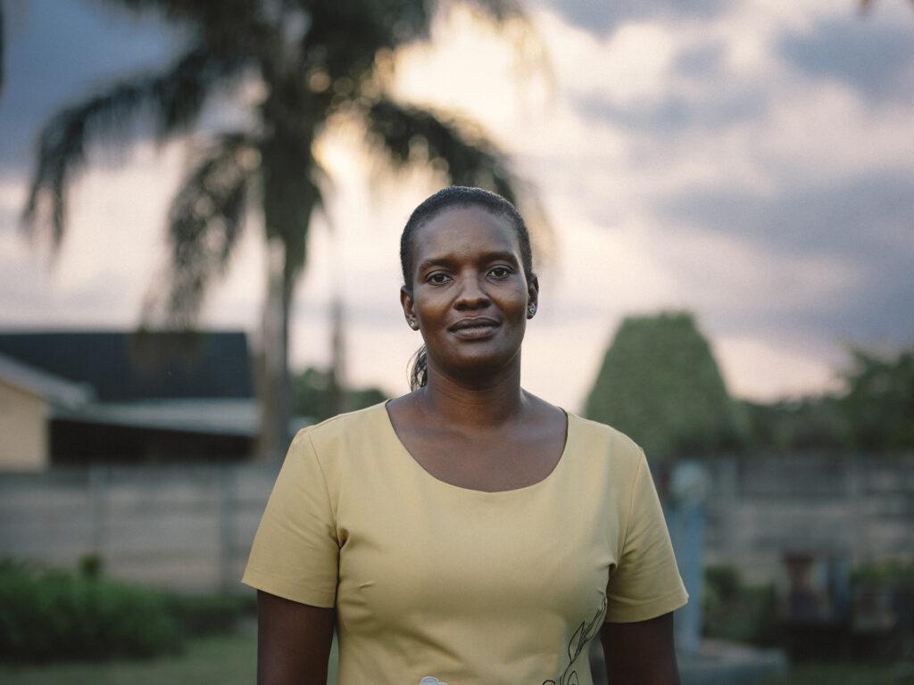 Bild av en kvinna med gul tröja som ser in i kameran. Bakom henne syns låga byggnader och gröna träd.