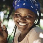 Närbild av en leende kvinna med en blå sjal i håret. Bakom henne syns träd eller buskage.