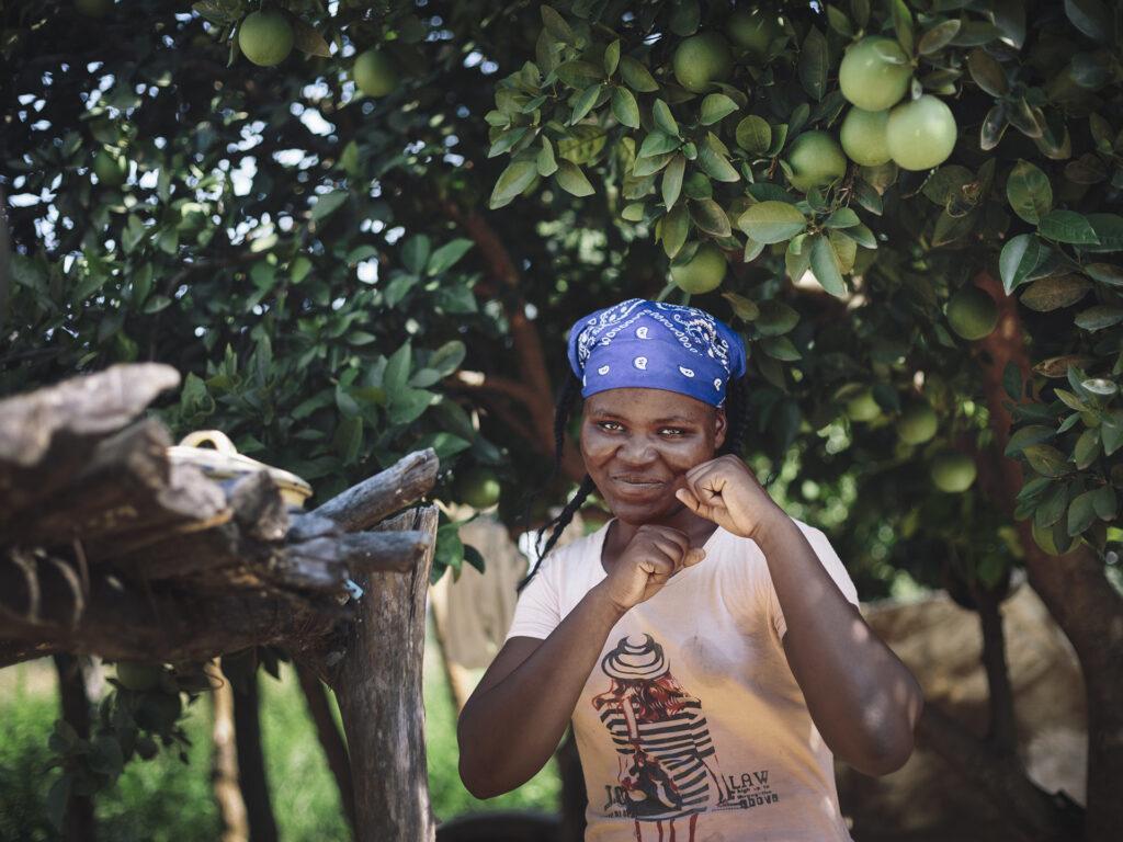 En kvinna står framför några träd. Hon ler och håller upp händerna i en boxnings-position. Hon har en blå sjal i håret.