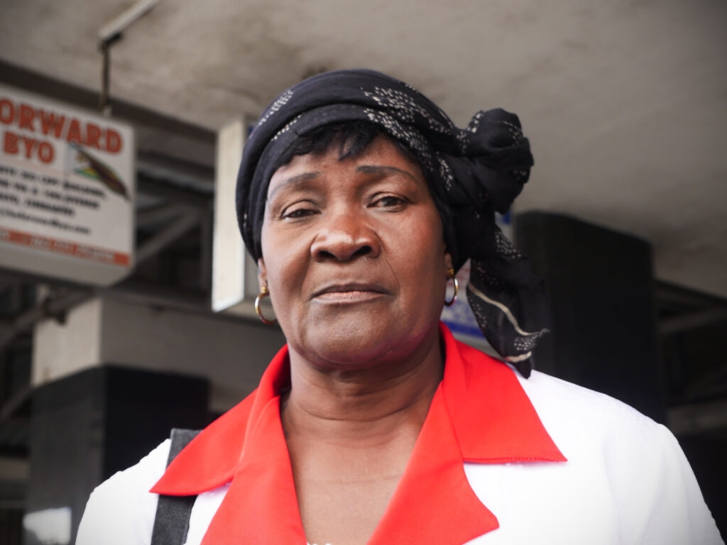 En kvinna med sjal i håret ser in i kameran. Bakom henne syns en grå byggnad.