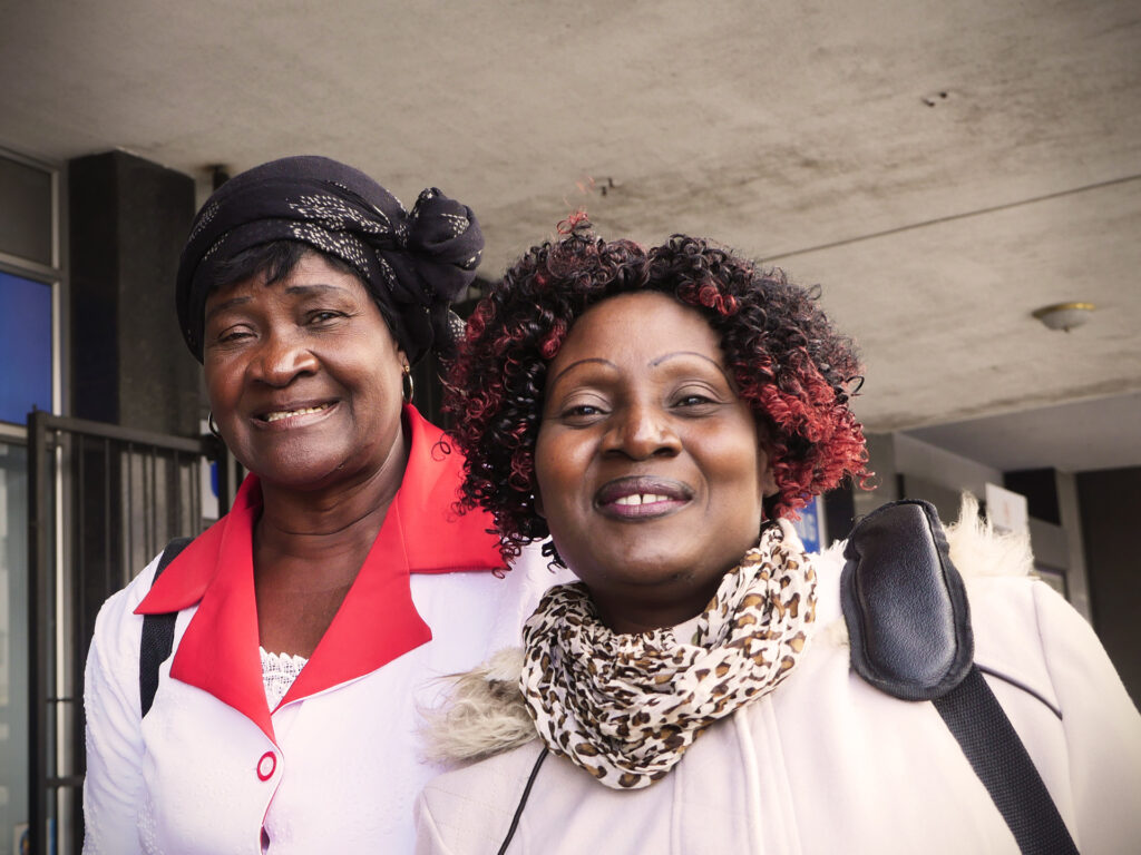 Två leende kvinnor ser in i kameran. Bakom dem syns en grå byggnad.
