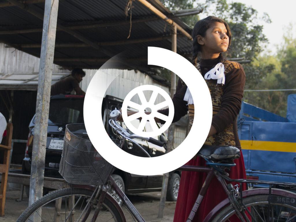 Flicka med en cykel på en innergård i Bangladesh