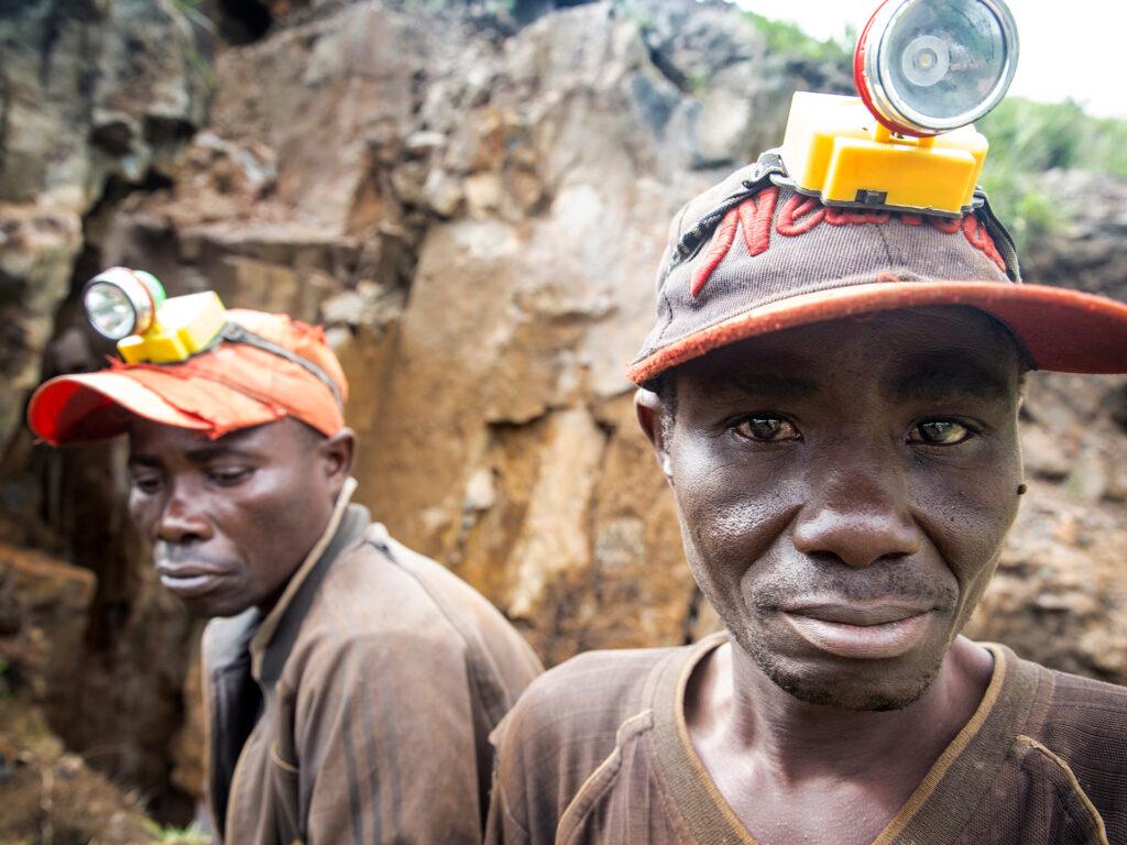 Två gruvarbetare i DRC utanför gruvöppningen.
