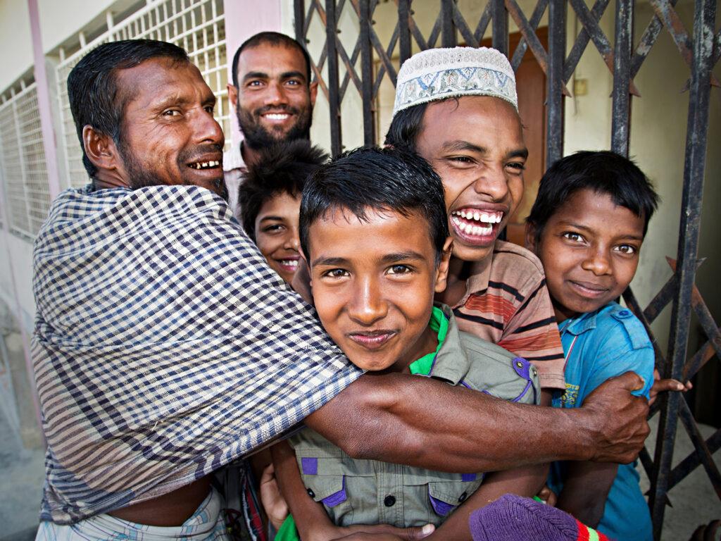 En grupp människor, både vuxna och barn, kramar varandra och ser glada ut.