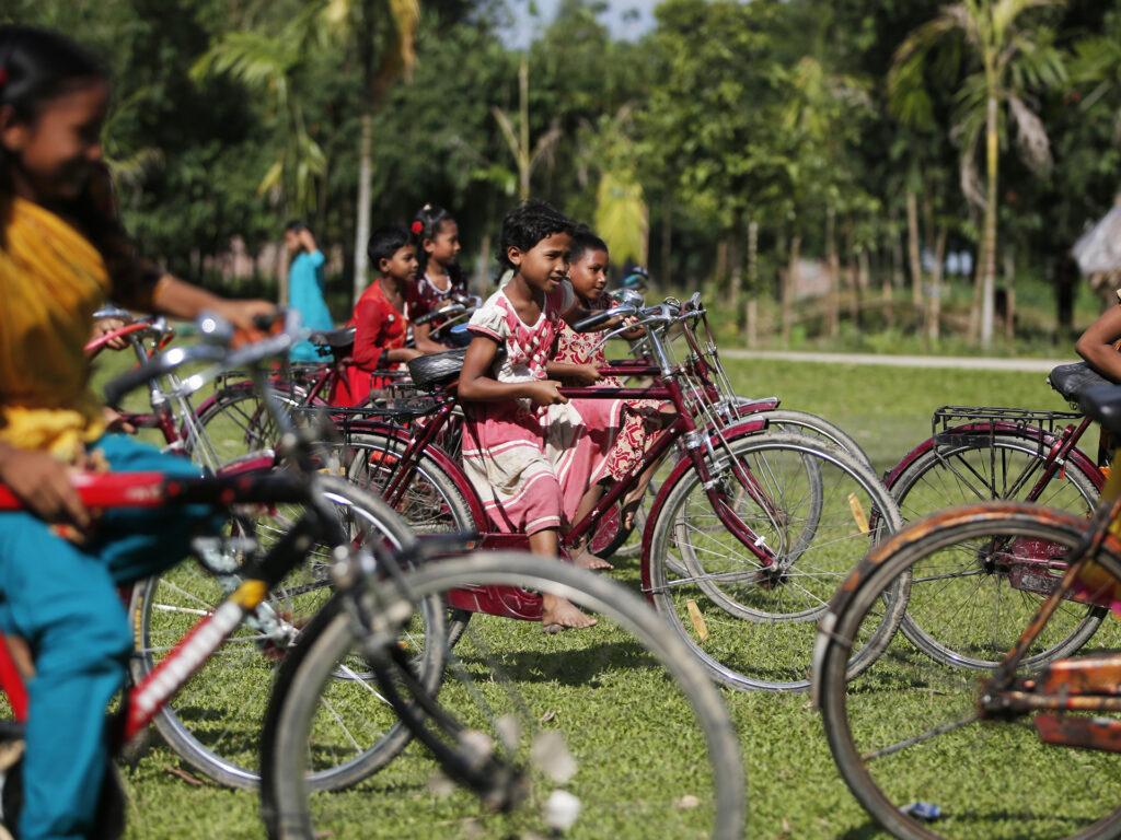 En liten flicka cyklar på en stor cykel. I bakgrunden är flera andra barn på cyklar.