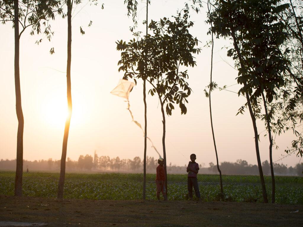 Två barn leker med en drake i solnedgången
