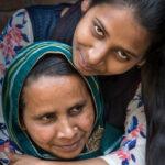 Bild på flicka som kramar om sin mamma.