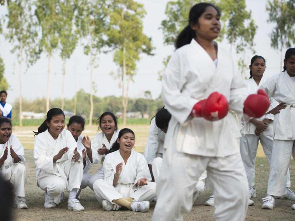 En grupp unga kvinnor sitter på marken och hejar på en annan kvinna som tränar karate.