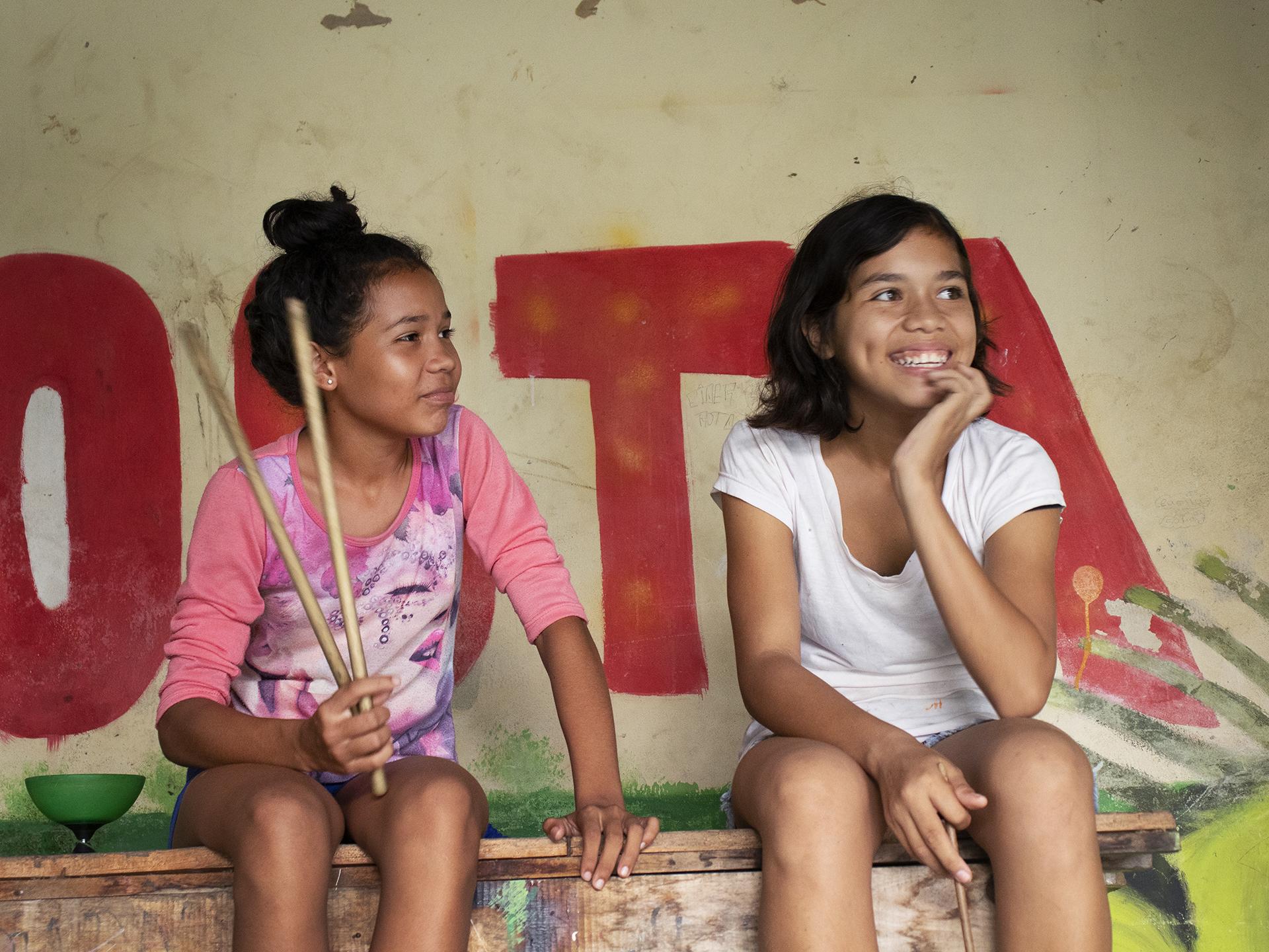 Två flickor sitter på en bänk och skrattar.
