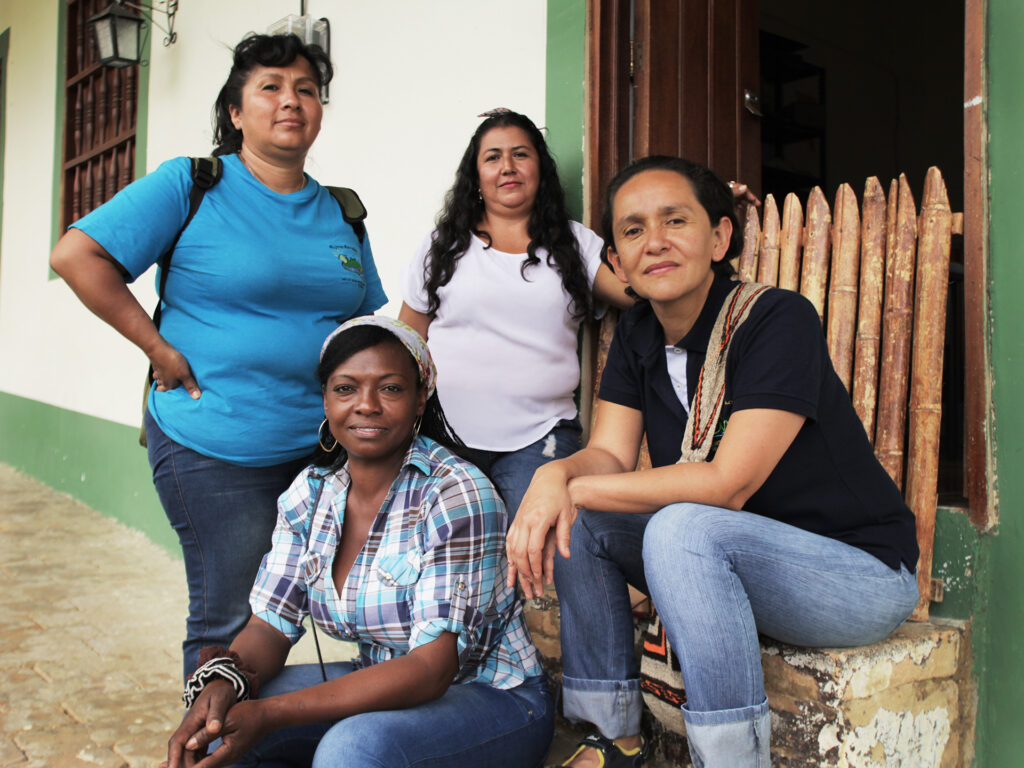 Fyra kvinnor sitter på en trappavsats och ser in i kameran.