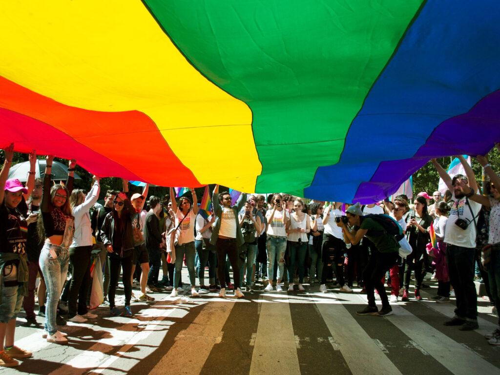 En stor regnbågsflagga täcker halva bilden. Under flaggan syns många människor som håller flaggan med sina händer.