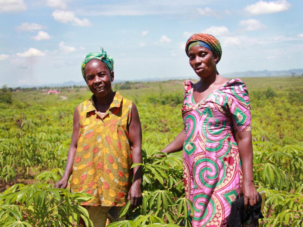Två kvinnor står i ett stort grönt fält.