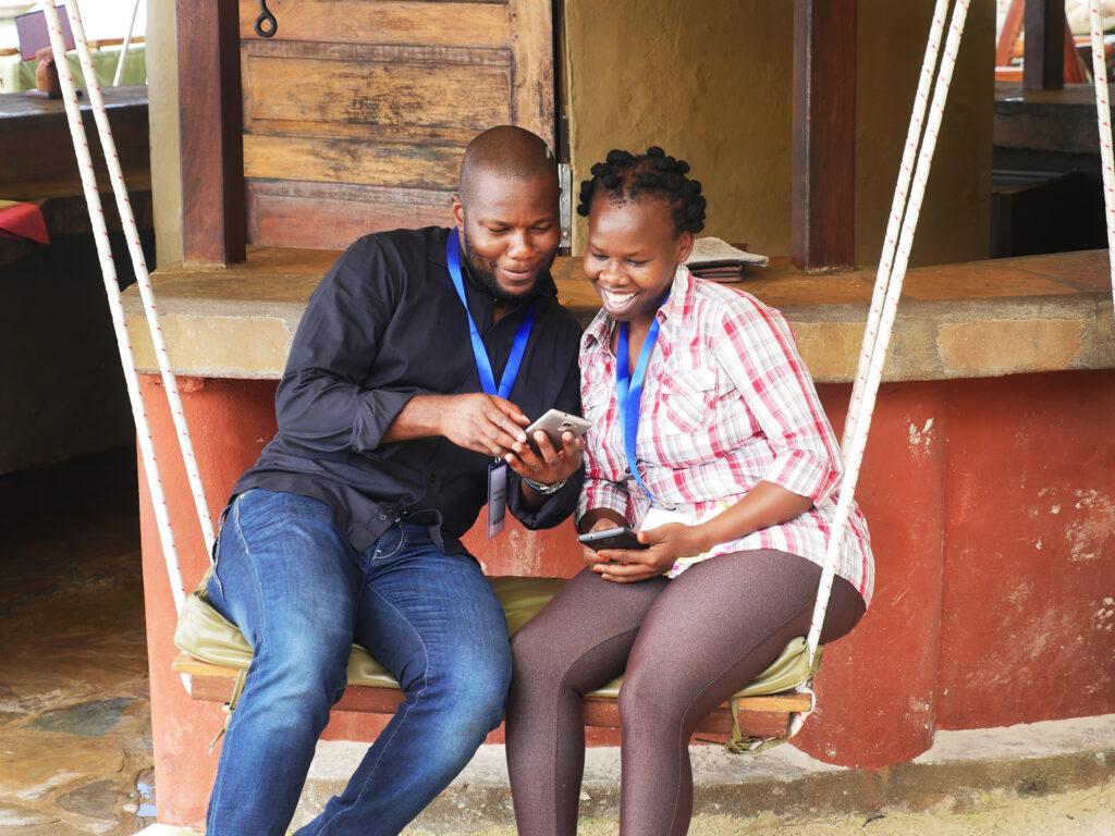 Två personer sitter i en hängmatta och tittar i en telefon.
