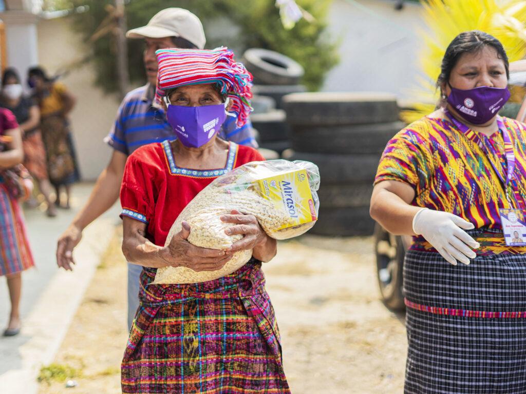 En äldre kvinna med munskydd håller i ett matpaket. I bakgrunden syns fler människor och en landsväg.