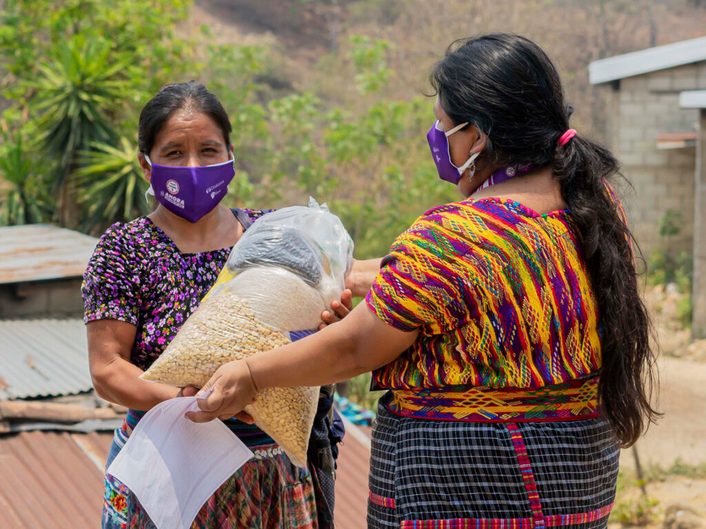 En kvinna med munskydd får en säck majs av en annan kvinna