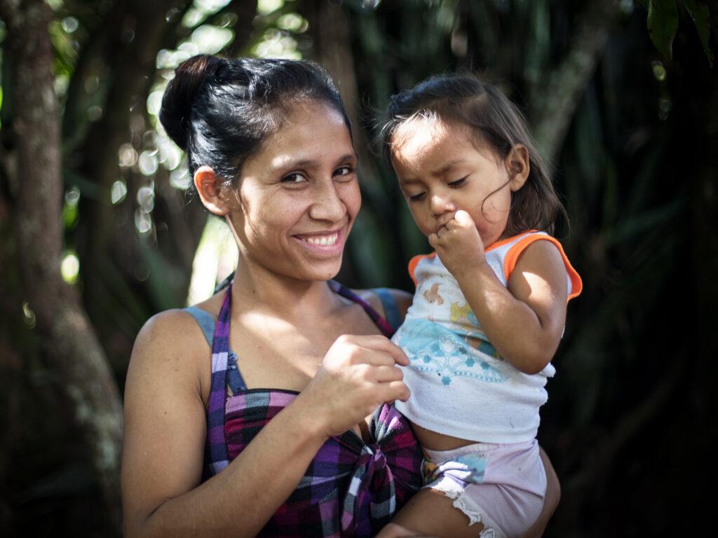 En leende mamma står med ett litet barn i famnen framför träd och buskage.