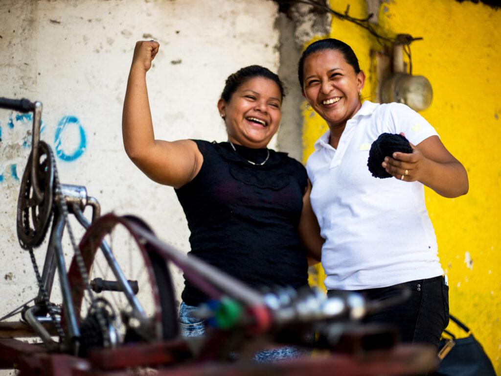 Två skrattande kvinnor står framför en uppochner-vänd cykel. Den ena kvinnan höjer armen med knuten näve.