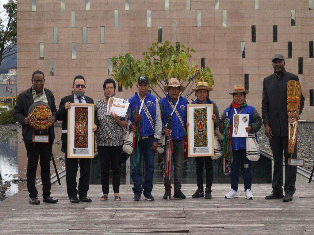 Colombianska människorättsförsvarare med priser i händerna framför byggnad i Bogota