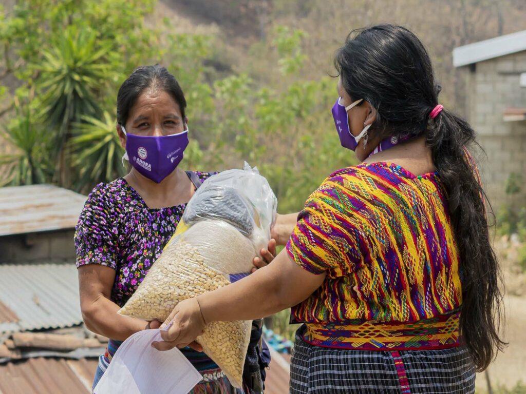 Två kvinnor i Guatemala med munskydd bär på matpaket