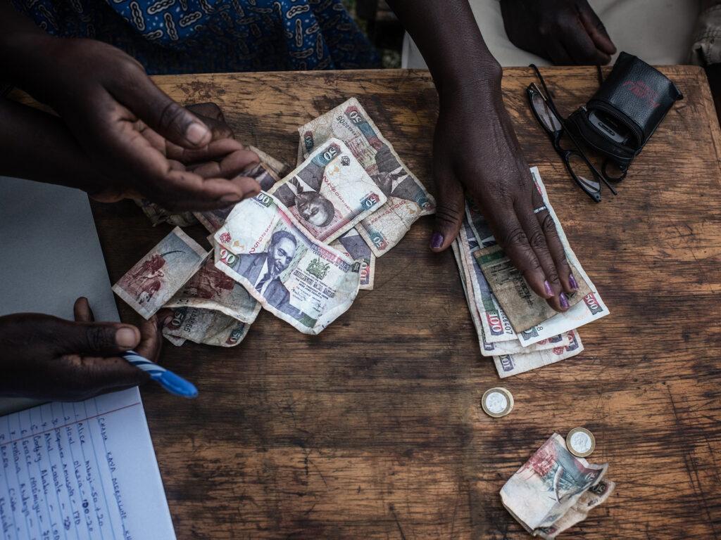 Händer över ett bord där det ligger mynt och sedlar.