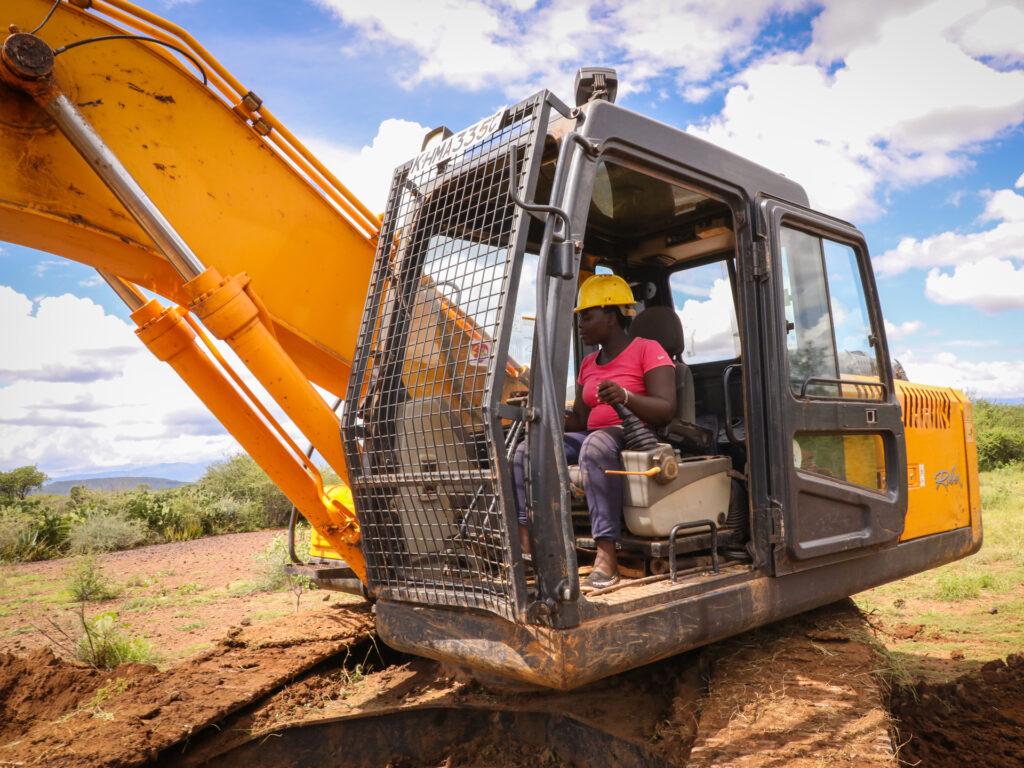En kvinns sitter i en grävmaskin och gräver