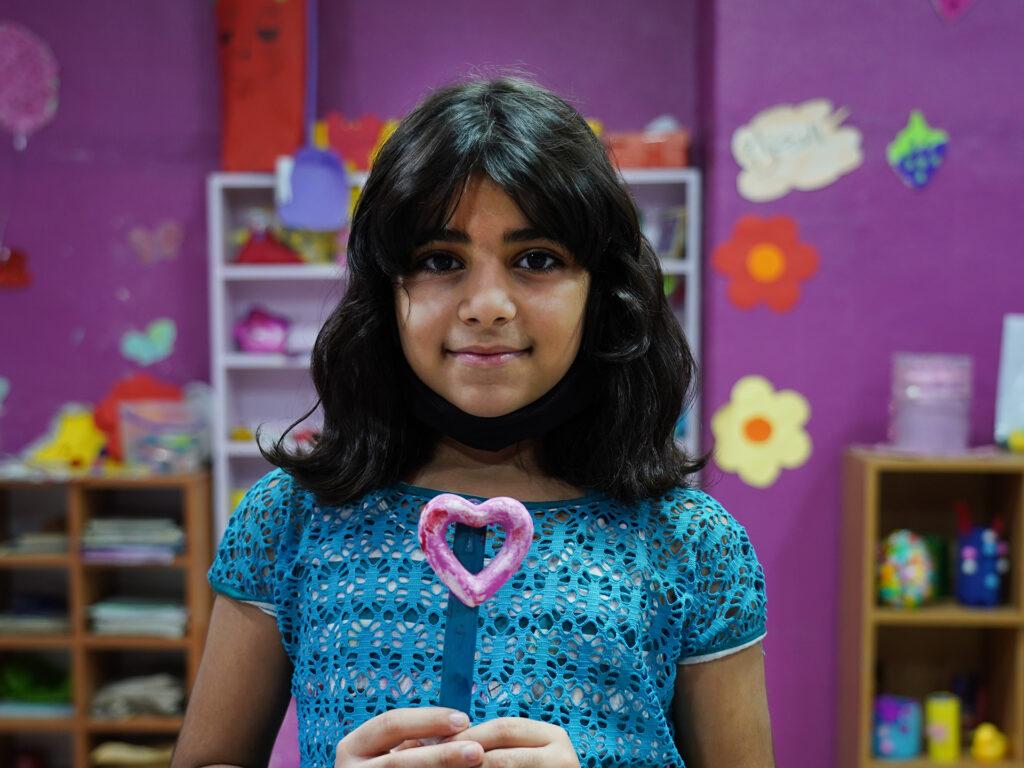 En flicka ser in i kameran. Hon håller upp ett hjärta i handen.