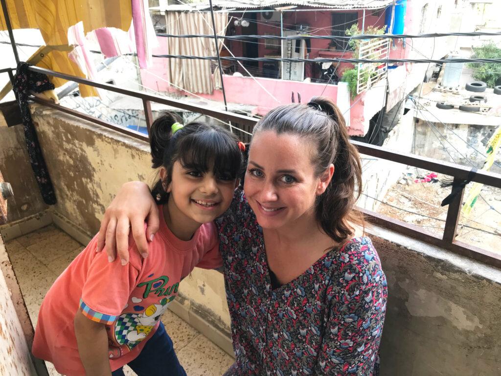 En flicka och en kvinna på en balkong håller om varandra och tittar in i kameran