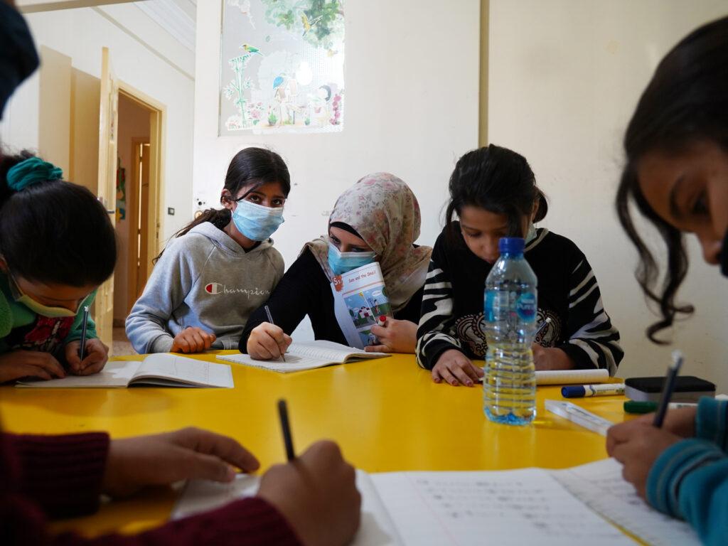 En lärare omgiven av elever