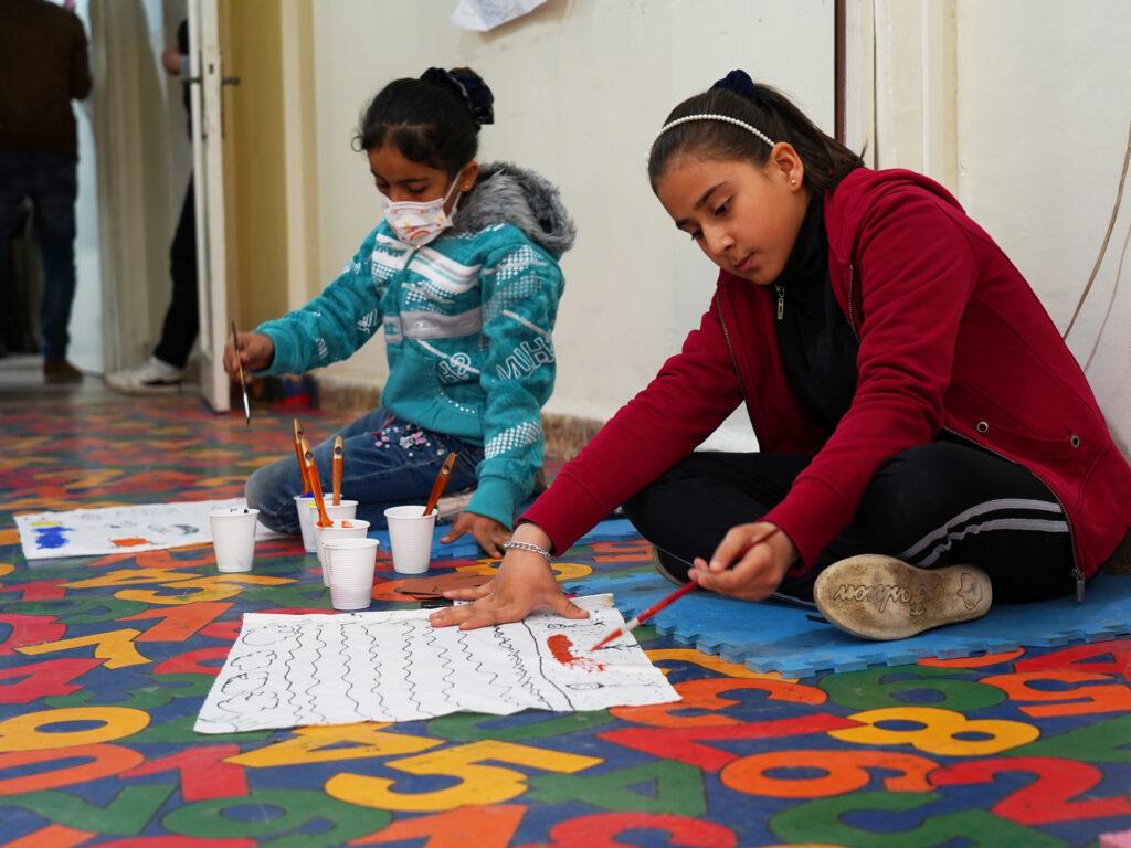 Två flickor sitter på ett golv och målar
