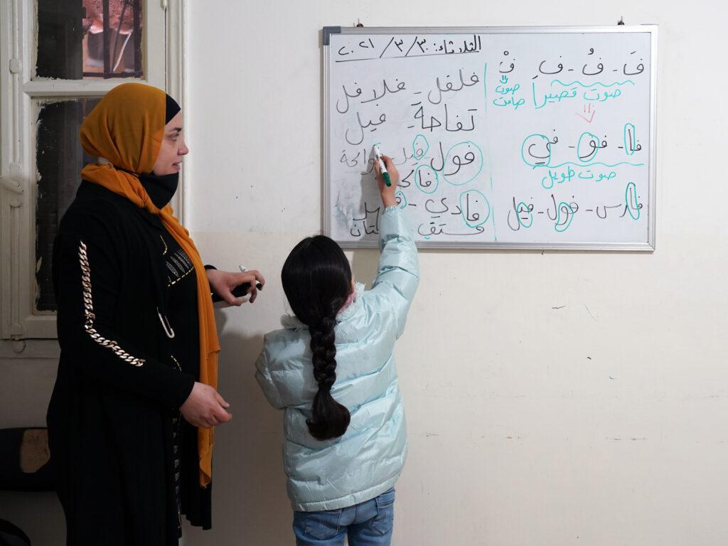En kvinnlig lärare och en elev som skriver på en whiteboard med text på arabiska