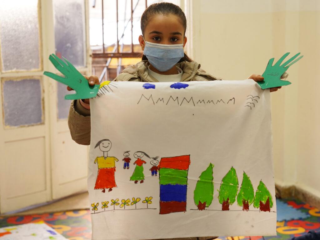 En flicka håller upp en teckning