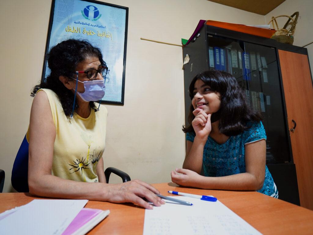 En kvinna med munskydd i samtal med en flicka på ett kontor