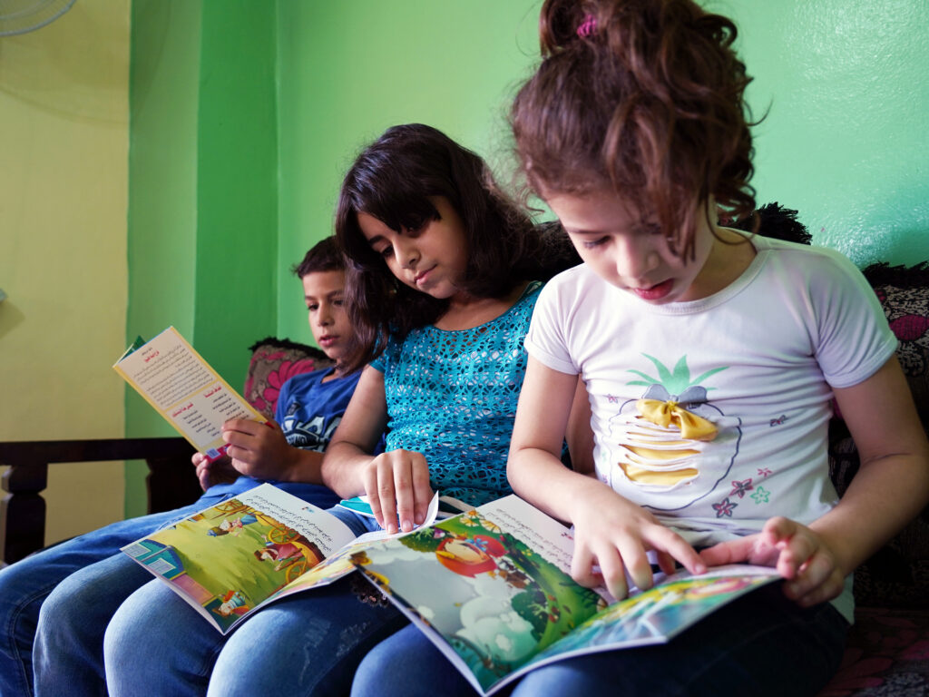 Tre barn i en soffa tittar i barnböcker
