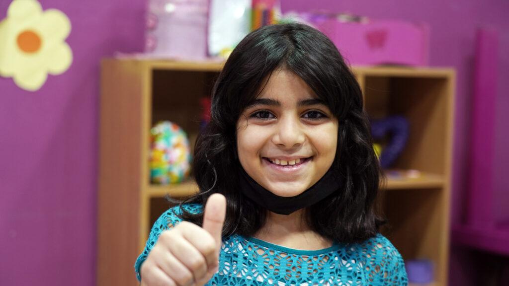 En flicka framför en bokhylla gör tummen upp