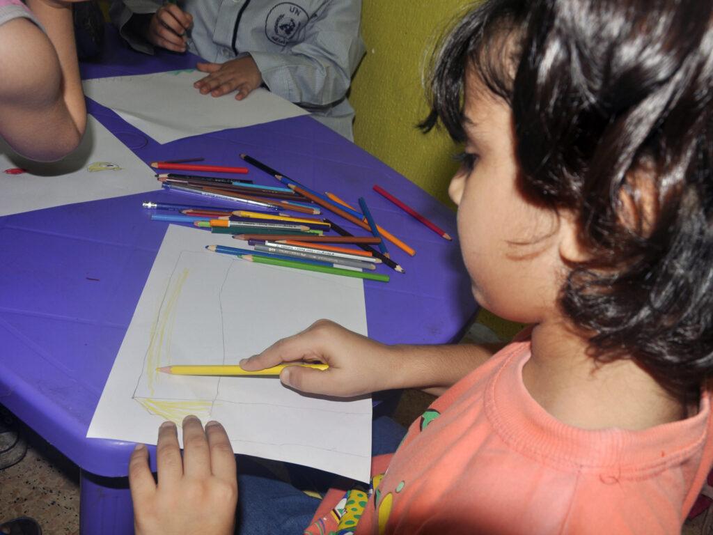 Barn som ritar vid ett bord