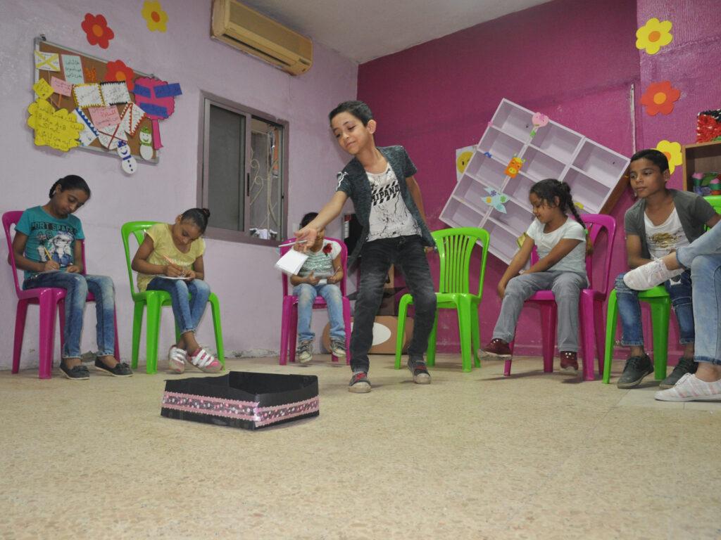 Barn sitter i ett rum med färgglada väggar. En lägger en lapp i en låda.