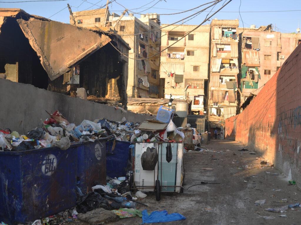 En trång gata med sopor och trasiga hus