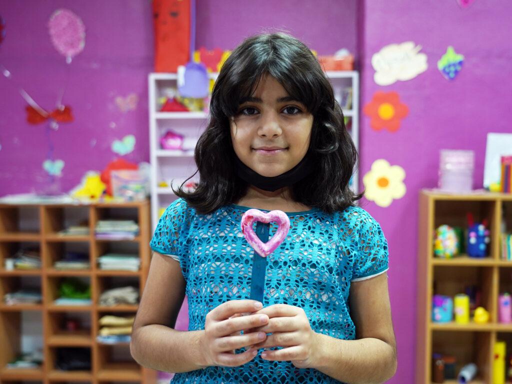 En flicka står i ett rum med färgglada bilder och håller ett pysselhjärta