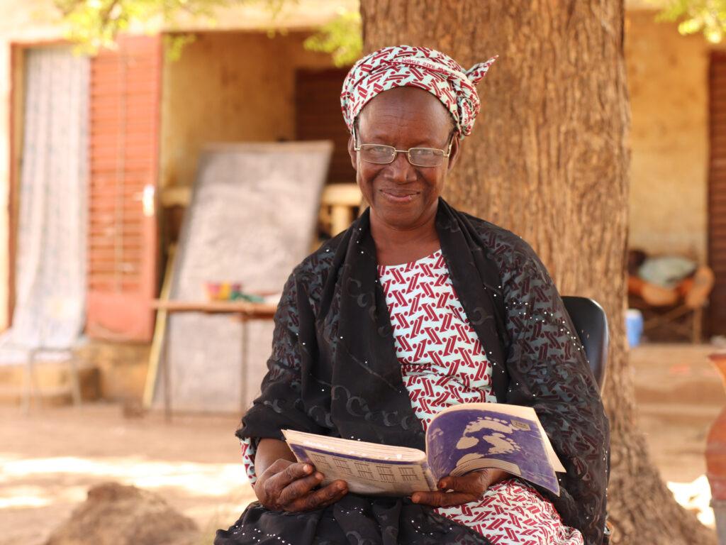 En äldre kvinna tittat in i kameran med en bok i knät